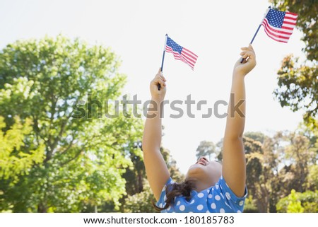 Low angle view of a young girl holding up two American flags at the park - stock photo
