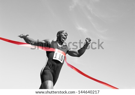 Low angle view of an African American male runner crossing finish line against blue sky - stock photo