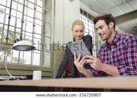Low angle view of an attractive young couple looking at a tablet together in an apartment or office with large windows - stock photo