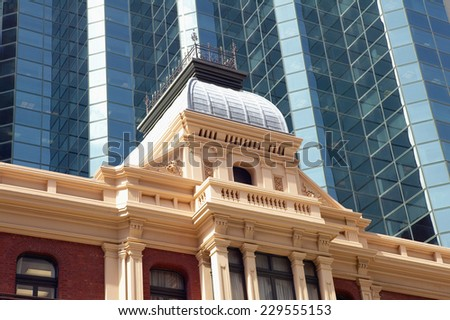 Low angle view of an ornate building in front of a glass skyscraper - stock photo