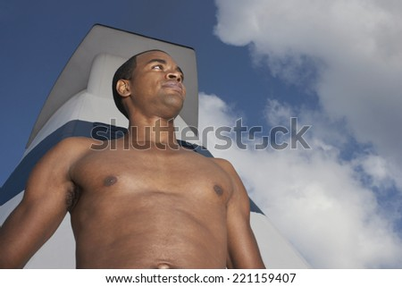 Low angle view of bare-chested African American man - stock photo