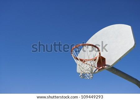 Low angle view of basketball hoop against blue sky - stock photo