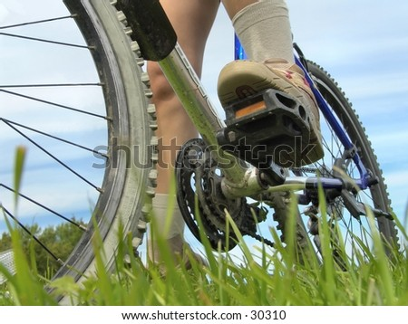 Low angle view of bike and feet. - stock photo