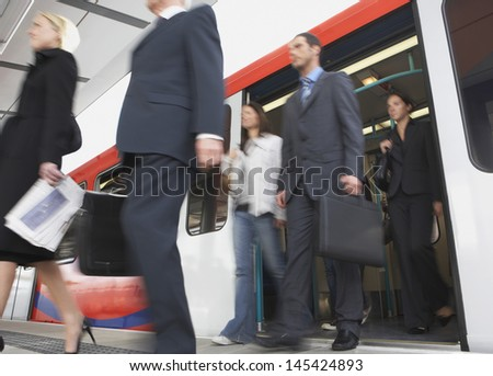 Low angle view of business commuters getting off a train - stock photo