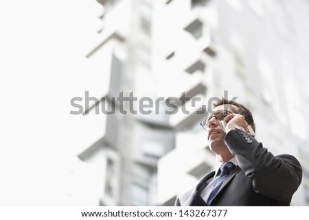 Low angle view of businessman communicating on mobile phone against tall building - stock photo