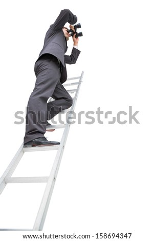 Low angle view of businessman standing on ladder using binoculars against white background - stock photo