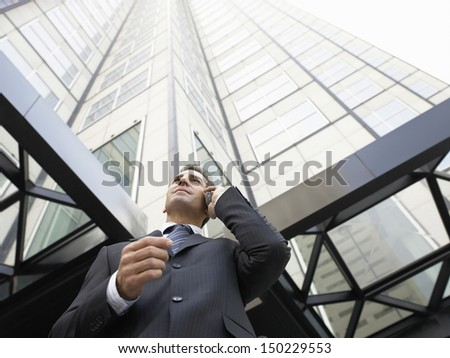 Low angle view of businessman using mobile phone against tall office building - stock photo