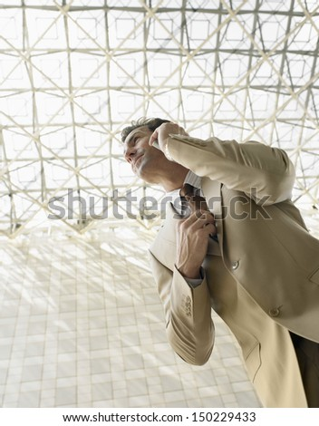 Low angle view of businessman using mobile phone under ceiling - stock photo