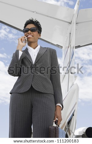 Low angle view of businesswoman using cell phone against wing tail of airplane at airfield - stock photo