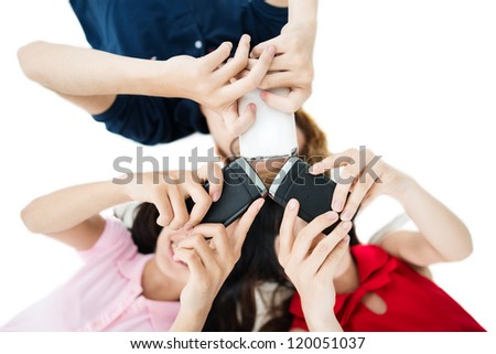 Low angle view of cell phones in hands of teenagers - stock photo