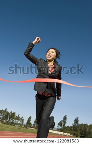Low angle view of cheerful business woman crossing the finish line of racing track against blue sky - stock photo