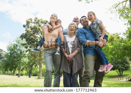 Low angle view of cheerful extended family standing at the park - stock photo