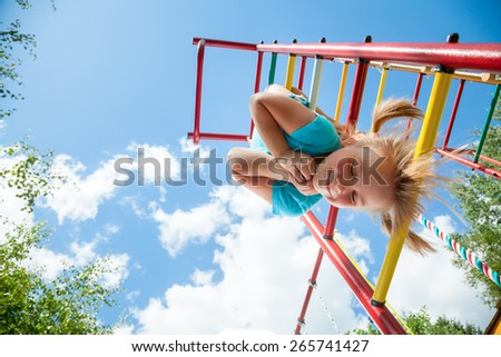 Low angle view of cute blond girl wearing blue tshirt hanging from a monkey bars. Girl is smiling with her eyes closed. Blue summer sky with clouds and tree leaves are seen in the background. - stock photo