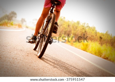 low angle view of cyclist riding mountain bike on public road - stock photo