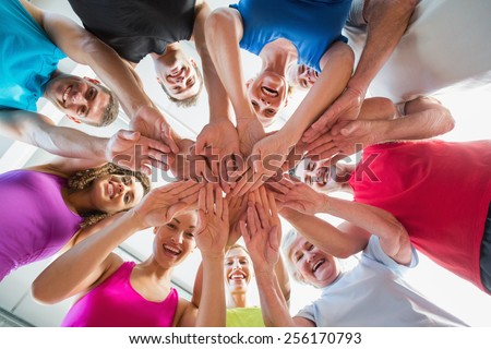 Low angle view of fit people stacking hands at health club - stock photo