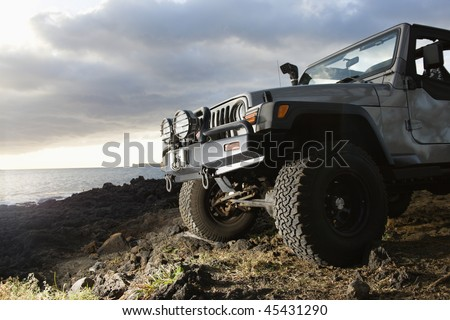 Low angle view of front of SUV on a rocky beach. Horizontal format. - stock photo