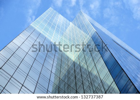 Low angle view of glass facade of tall office building on blue sky - stock photo