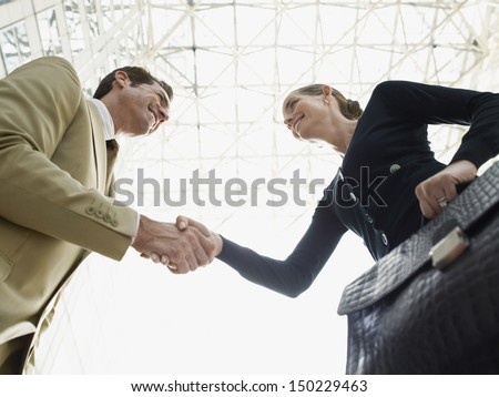 Low angle view of happy businessman and businesswoman shaking hands against ceiling - stock photo