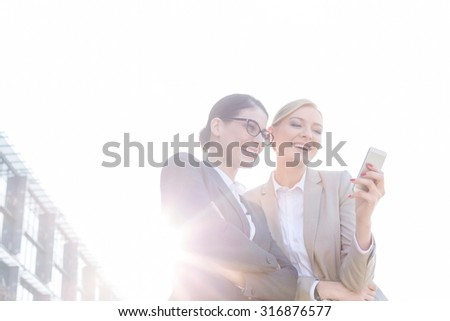 Low angle view of happy businesswomen using smart phone against clear sky on sunny day - stock photo