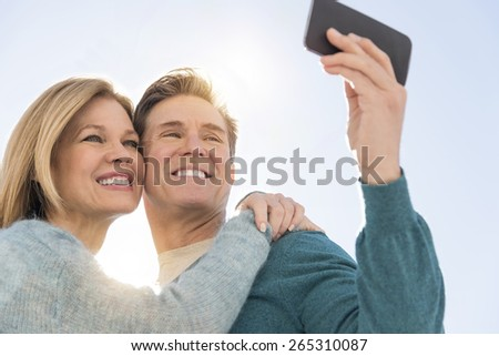 Low angle view of happy mature couple taking self portrait through cell phone against sky - stock photo