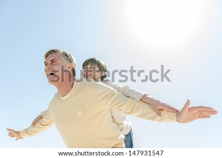 Low angle view of happy mature man looking away while giving piggyback ride to son against clear blue sky - stock photo