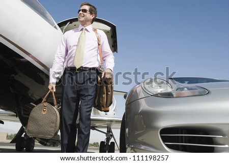 Low angle view of happy middle aged businessman standing with luggage on airfield - stock photo