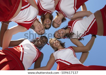 Low angle view of happy multiethnic cheerleaders forming huddle against clear sky - stock photo
