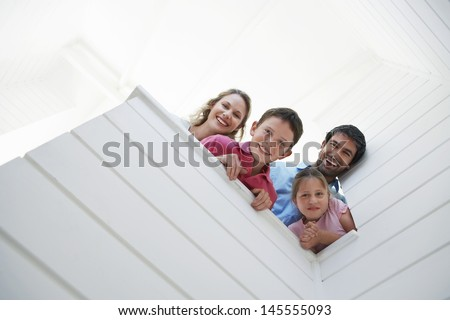 Low angle view of happy parents with children looking over white wall - stock photo