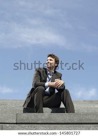 Low angle view of happy young businessman sitting on steps against sky - stock photo