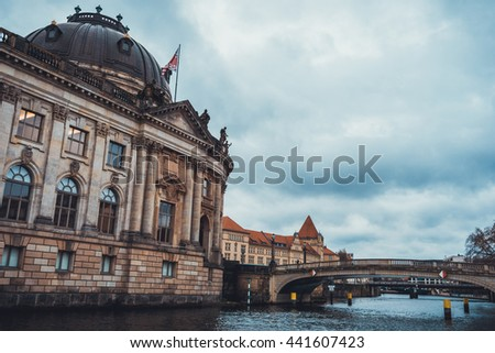 Low Angle View of Historical Bode Art Museum as seen from River with Small Bridges Crossing to Museum Island on Overcast Day with Storm Clouds, Berlin, Germany - stock photo