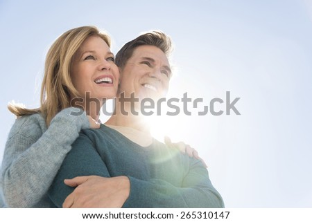 Low angle view of loving couple smiling together while looking away against clear sky - stock photo