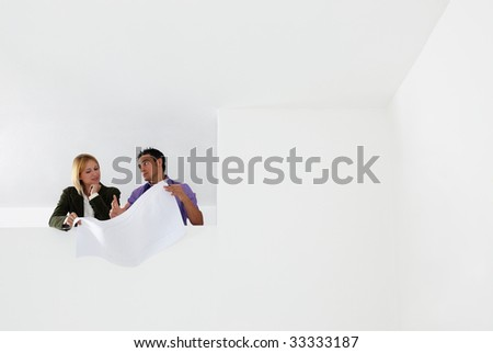 low angle view of male architect and woman examining blueprints. Copy space - stock photo