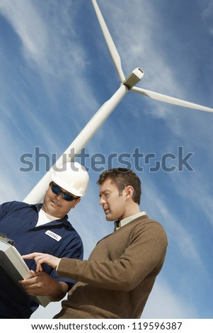 Low angle view of male engineers in discussion against wind turbine - stock photo