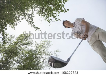 Low angle view of man getting ready to hit the golf ball - stock photo