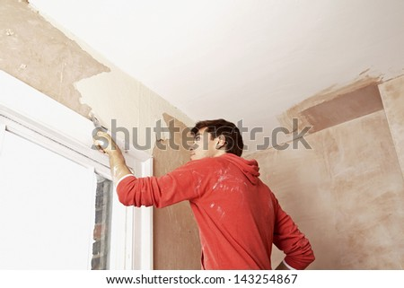 Low angle view of man scraping paint off wall in unrenovated room - stock photo