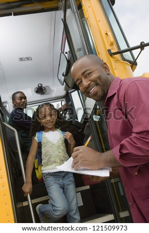 Low angle view of man writing on paper while little girl getting down from school bus - stock photo