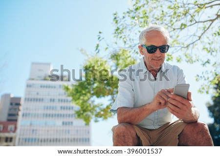 Low angle view of mature man sitting outdoors using mobile phone. Mature tourist resting outside in the city and reading text message on his cell phone. - stock photo