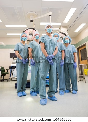 Low angle view of multiethnic medical team standing in operation room - stock photo