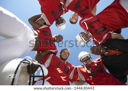 Low angle view of rugby players with coach forming huddle against clear sky - stock photo