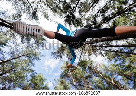 low angle view of runner jumping and running in forest. healthy active lifestyle - stock photo