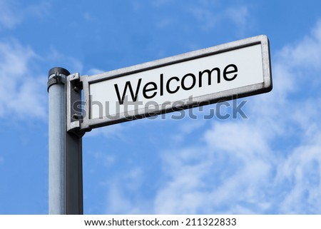 Low angle view of signpost with Welcome sign against sky - stock photo
