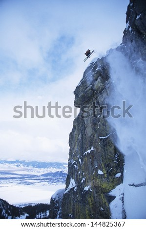 Low angle view of skier jumping from mountain cliff - stock photo