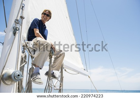 Low angle view of smiling man sitting on yacht boom - stock photo