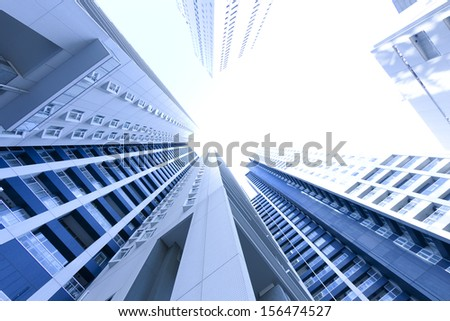 Low angle view of tall high raised modern buildings - stock photo