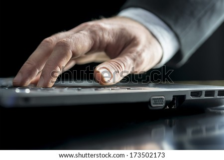 Low angle view of the hand of a businessman typing on a laptop computer keyboard inputting data or surfing the internet - stock photo