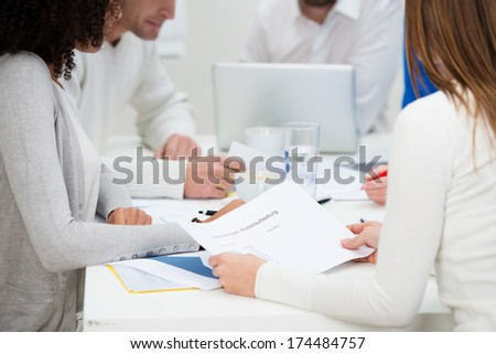 Low angle view of the hands and paperwork on the table of a group of business colleagues in a meeting as they have a brainstorming session - stock photo