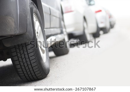 Low angle view of tire of car in traffic jam - stock photo