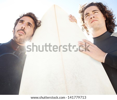 Low angle view of two friends surfers standing on a beach with a sunny blue sky in the background and the sun shining through, being thoughtful. - stock photo
