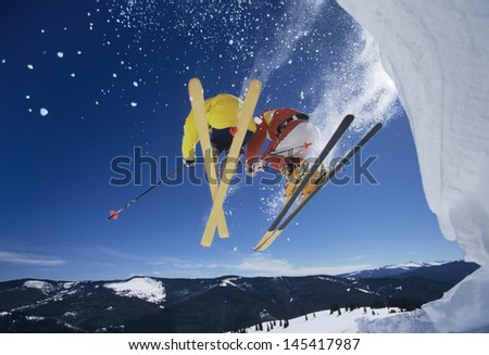 Low angle view of two skiers launching off snow bank hitting the slopes - stock photo