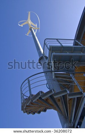 Low angle view of vertical axis wind turbine attached to building against a clear blue sky. Includes metal spiral staircase. Slight motion blur on turbine blades. - stock photo